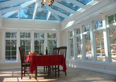 A pristine white conservatory outfitted with a dining table, chairs, tablecloth, and wine spread reveals a forest beyond its windows