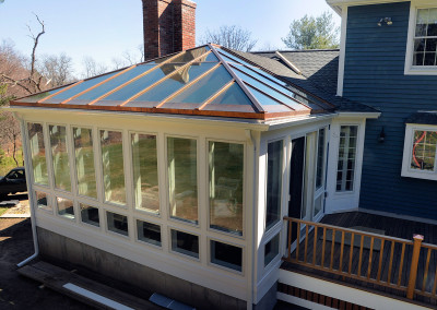 A conservatory in the final stages of construction sits adjacent to the deck of a beautiful blue New England home