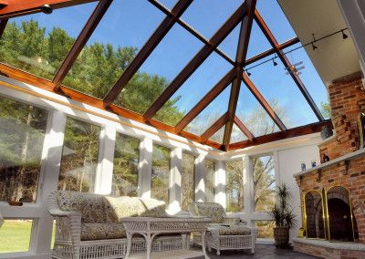 A pastel colored patio couch sits beside a beautiful fireplace under a custom Sunspace Design glass roof in this New England conservatory installation