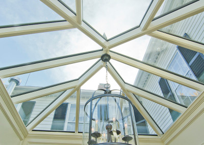 The sun peeks through clouds, casting rays of light which enter this gorgeous New England glass enclosure via a dramatic roof lantern