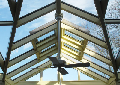 An angled Sunspace Design glass roof system featuring skylight windows and hanging ceiling fans