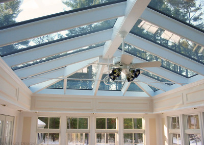 A large, multi-paned glass roof system transmits the cool blue light of the morning sun into a Sunspace Design sunroom
