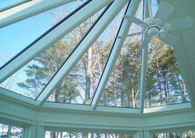 A fully custom octagonal glass roof sits above a glass conservatory located in Kittery Point, Maine