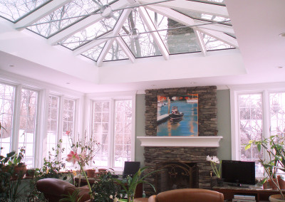 A bright white family sunroom features an impressively large glass roof system, flooding the room with natural sunlight