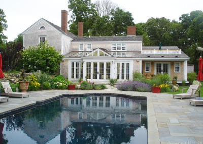 An exterior photo of a gorgeous backyard patio, pool, and garden in front of a custom glass Sunspace Design conservatory