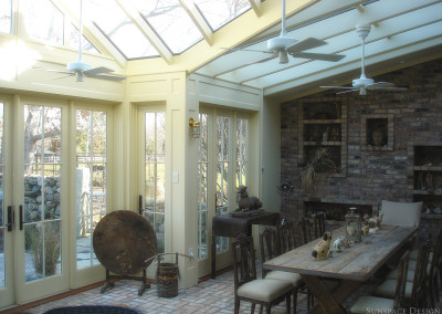 An interior view of a conservatory showing a beautiful seating area, collection of artifacts, custom cabinetry, sink, and countertop