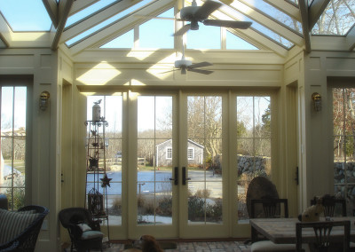 A photo featuring a family pet curled up in front of French doors leading out of a glass conservatory into the residence's pool and garden area