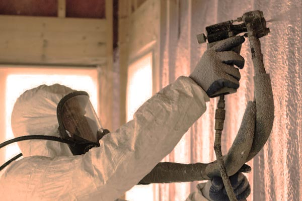 A Sunspace Design team member wearing protective gear and applying spray insulation to the stick frame walls of a new glass enclosure
