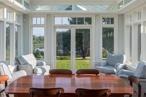 A polished wood table and adjacent seating area are positioned inside a large glass conservatory with elegant French doors and tall windows on all walls
