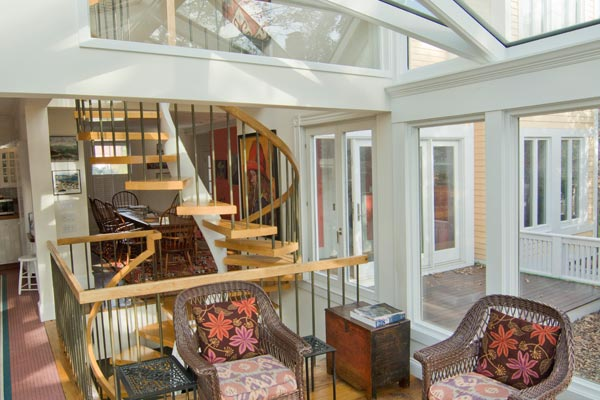 A large glass conservatory annexed directly to the interior space of a home with a spiraling staircase connecting three separate floors