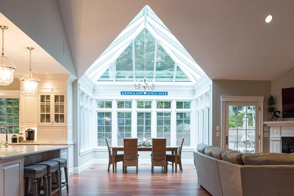 A modern conservatory space with tall windows and angular glass roof components separates the kitchen and living areas of an open concept floor plan