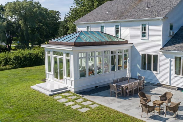 An elegant conservatory is annexed to the rear of a farm-style home in the backyard space adjacent to a winding river and stone tiled patio seating area