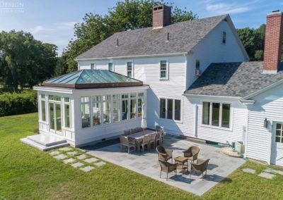 A bright white custom glass conservatory is annexed directly to the rear of a home in the space beside a tiled outdoor patio and adjoining barn