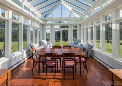 A large polished wooden table sits atop the hardwood flooring of a custom glass conservatory enclosure with white walls, tall windows, French doors, and glass roofing
