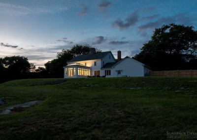 A brightly illuminated glass conservatory spills light onto the surrounding home and backyard of this gorgeous farm estate in the dusklight of a fading day