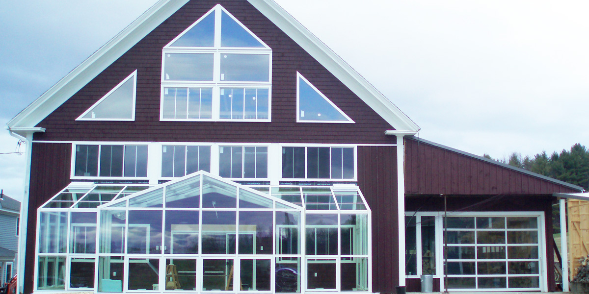 An exterior view of a classic Maine barn that has been outfitted with a custom aluminum year-round greenhouse by Sunspace Design