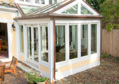 Conservatory Exterior with Tall Glass Windows and French Doors