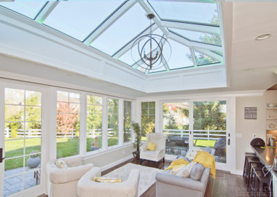 An interior view of sunlight pouring through tall windows and a custom double hip skylight onto a luxurious seating area
