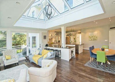 An interior angle of a custom orangery-style skylight beside a seating area and gorgeous open concept kitchen