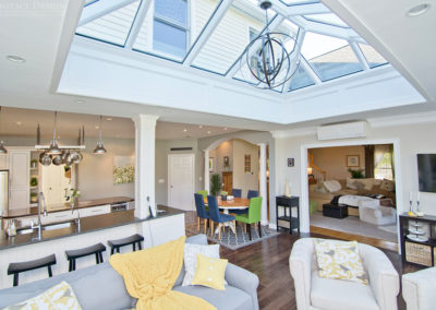 An interior view of a custom New England glass roof with a unique lighting fixture spilling light into an open concept floor plan