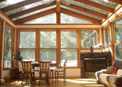 The interior of a traditional glass sunroom with tall windows, a glass gable roof, wood flooring, wood trim, and matching moldings