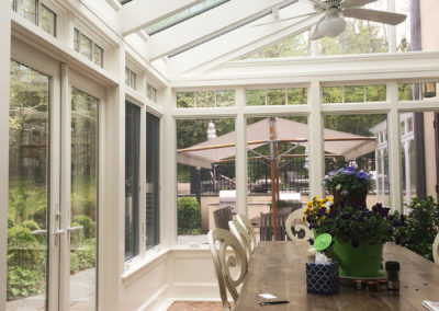 A view within a conservatory toward an exterior patio which is connected via convenient French doors