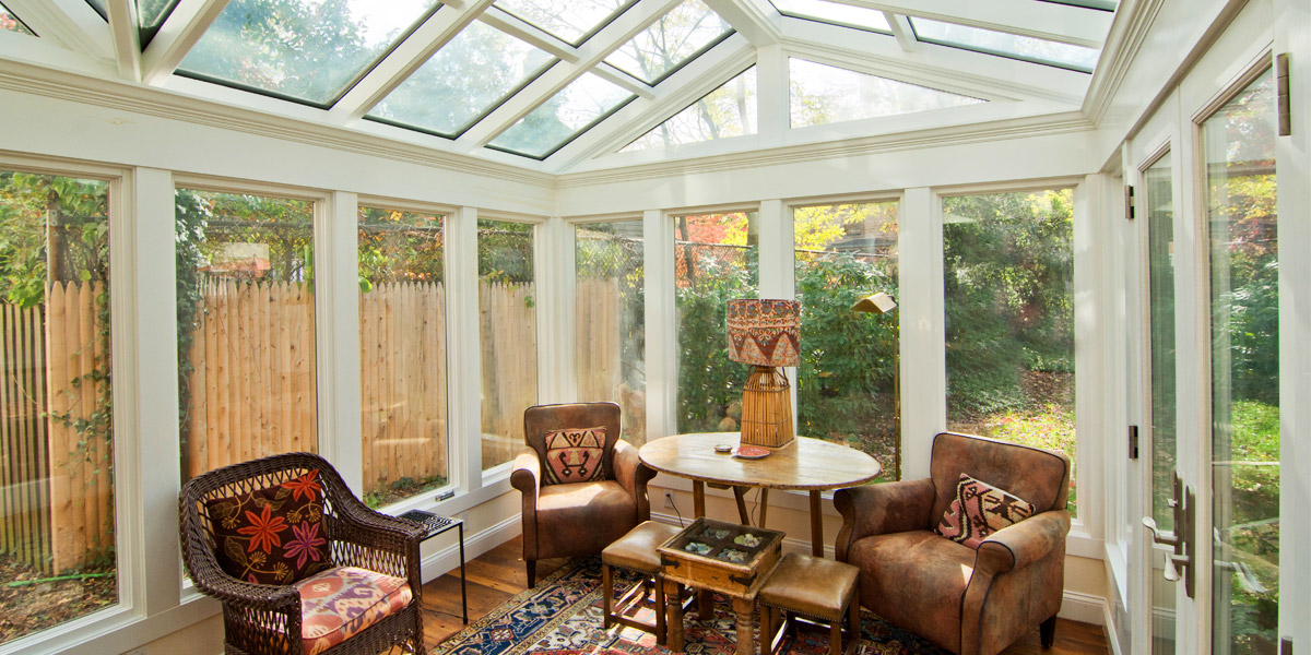 An interior view of an attractive seating area within a beautiful glass conservatory designed and built by Sunspace Design