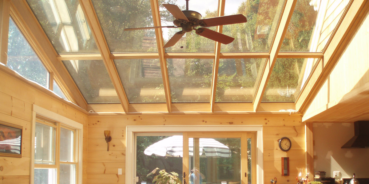 A close view of the sloped glass roof of a kitchen-sunroom hybrid addition designed and built by Sunspace Design in Gloucester, Massachusetts