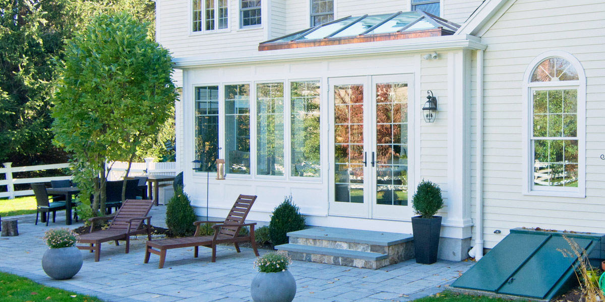 A photo of the exterior of a gorgeous orangery-style custom glass addition with a stunning double hip skylight in Medfield, Massachusetts