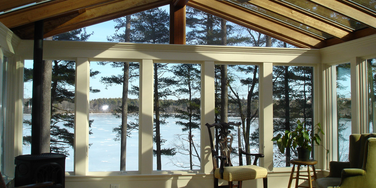 A stunning view through the tall Andersen windows of a gable-style sunroom revealing a sprawling frozen lake in the background