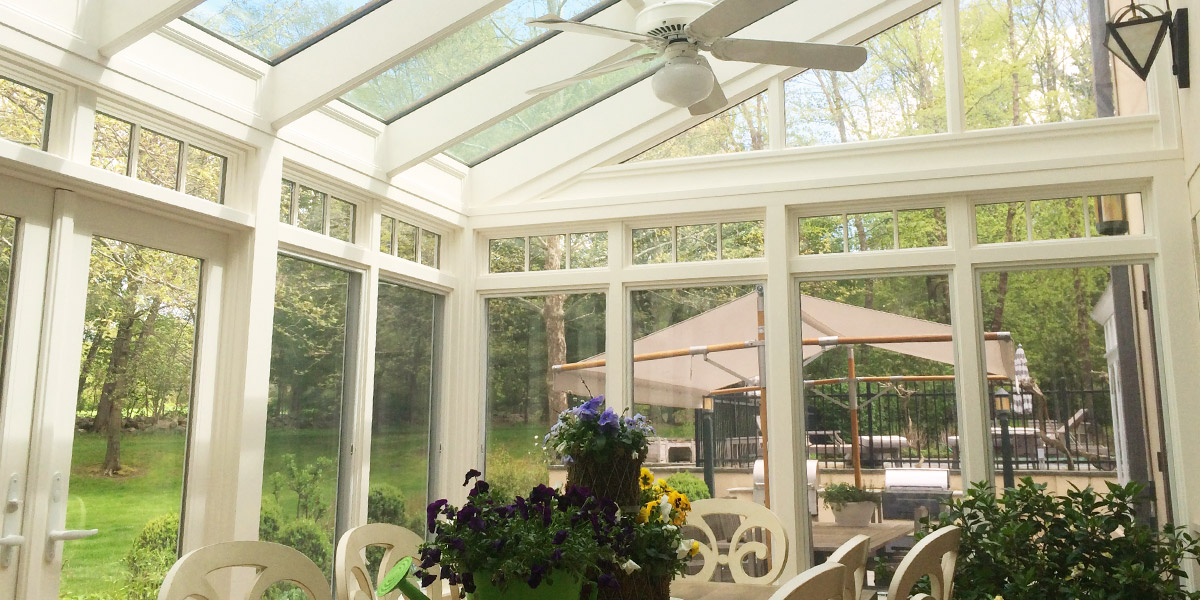 A view through the windows of a traditional conservatory facing an outdoor garden, patio, and seating area