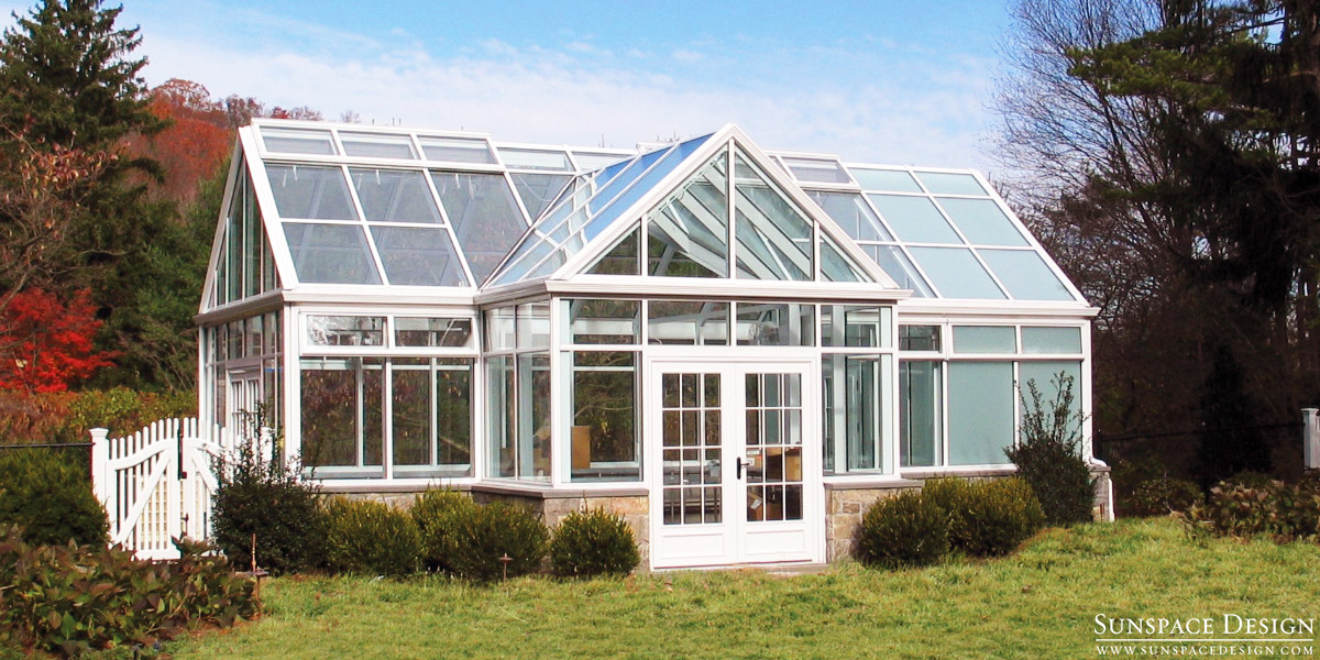 A photo of a white outdoor greenhouse with nearby shrubbery taken on a sunny day
