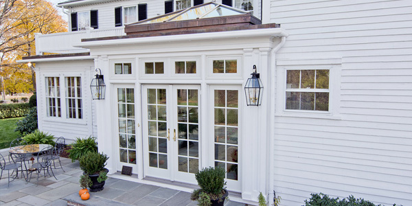 An exterior photo of a custom colonial orangery and central skylight system matching the existing architecture of a Shrewsbury, Massachusetts home