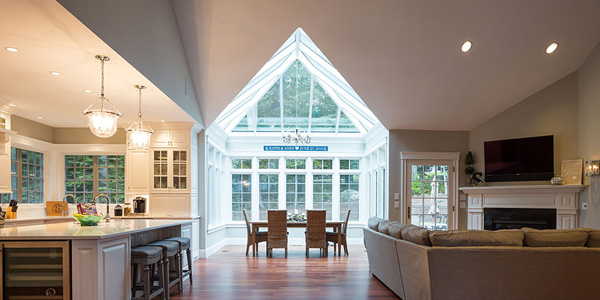A photo of a luminous sloped roof conservatory flooding light into adjacent kitchen and family room spaces in Rye, New Hampshire