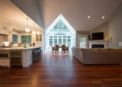 A brightly lit kitchen is to the left, a glass conservatory addition used as a dining space is straight ahead, and a comfortable seating area is to the right
