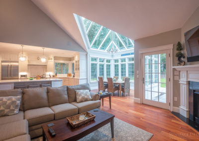 An interior view of a glass conservatory with an angular glass ceiling taken from the perspective of the corner fireplace