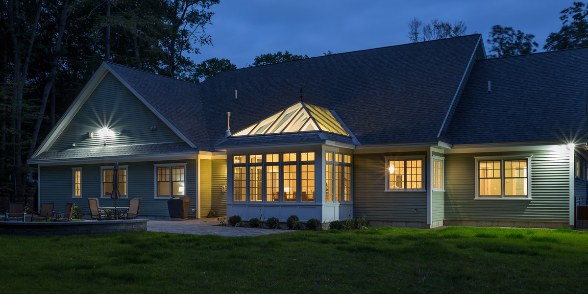 An exterior nighttime shot of a stunning glass conservatory located in Rye, New Hampshire