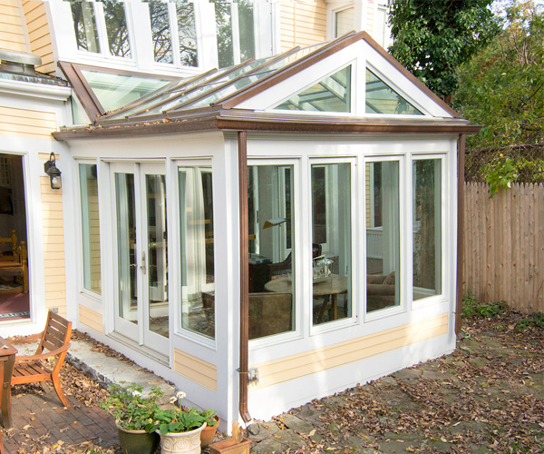 A bright, contemporary conservatory featuring large, clear glass window panes and a simple, open design