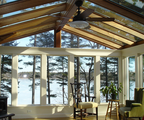 An interior view of a spacious, gable style sunroom with a double-sloped roof and an impressive lakeside view