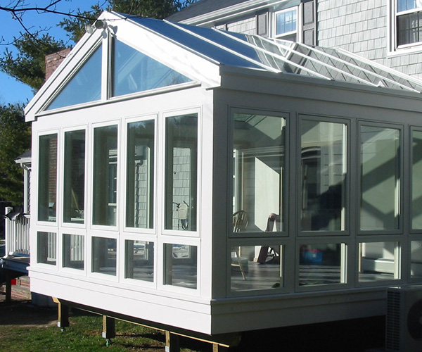 An elevated contemporary sunroom with floor-to-ceiling windows and large glass spans in the roof
