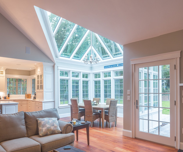 A conservatory with sloped glass roof elelents flooding the living space with natural light in Rye, New Hampshire