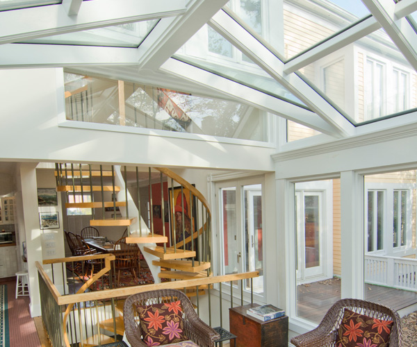 An interior-facing view of a spiral staircase from a bright contemporary conservatory located in Harvard Square, Cambridge, Massachusetts