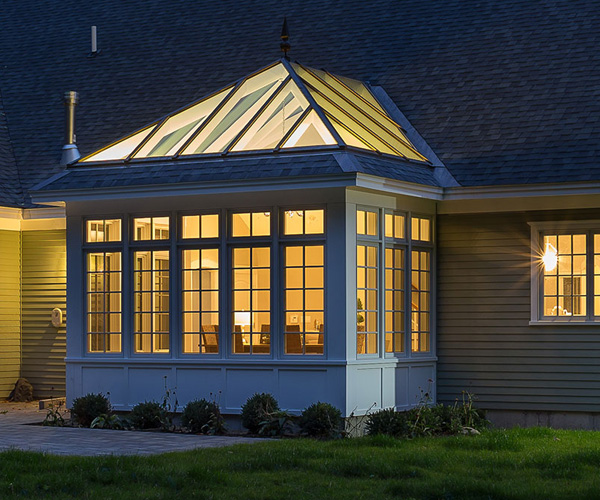 A stunning nighttime photograph of a Sunspace Design conservatory casting warm light onto the client's yard in Rye, New Hampshire