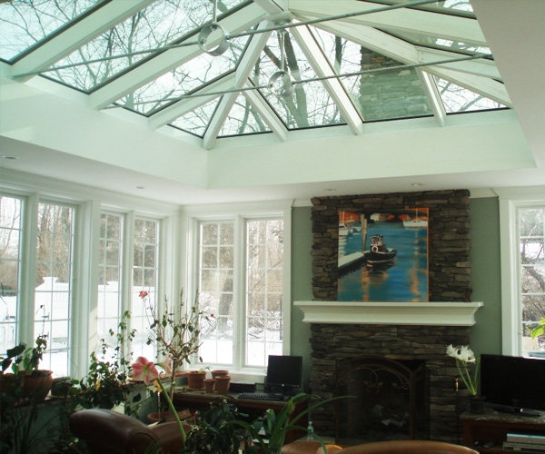 A large, double-hip skylight illuminates a family room with a fireplace in Newbury, Massachusetts