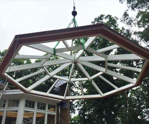 An octagonal skylight being crane-lifted into place by Sunspace Design's expert team for a Lexington, Massachusetts project