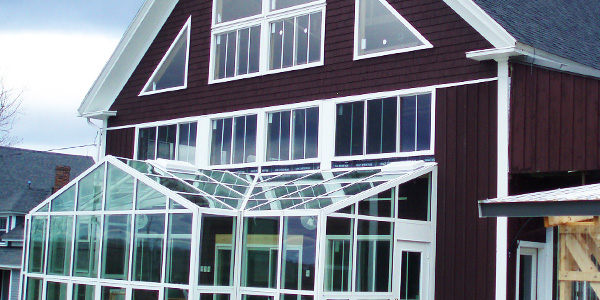 A barn greenhouse project located in Turner, Maine featuring automated roof vents and an aesthetic matching the existing architecture