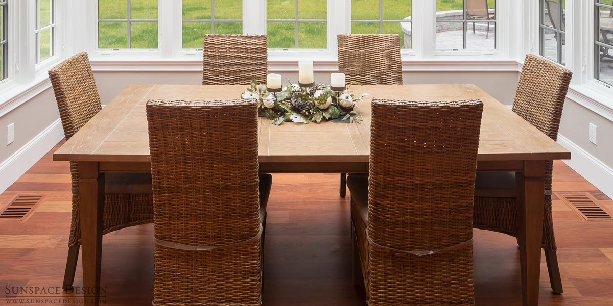 An interior view of a Rye, New Hampshire glass conservatory's dining area with gorgeous mahogany wood flooring
