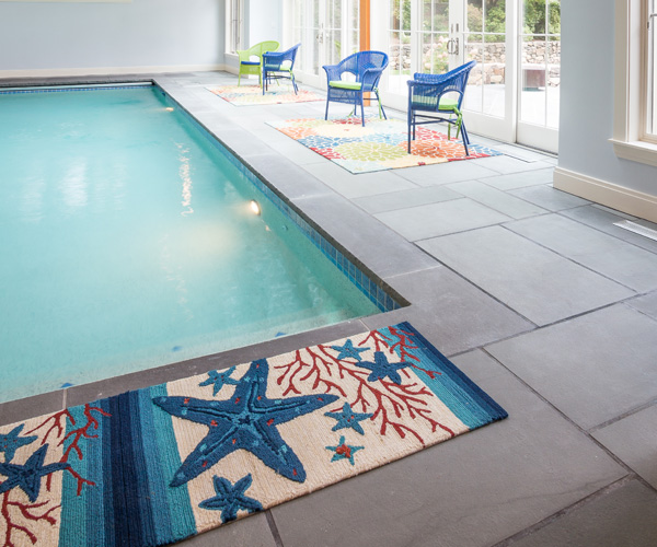 An interior view of a Carlisle, Massachusetts indoor swimming pool enclosure featuring bluestone flooring