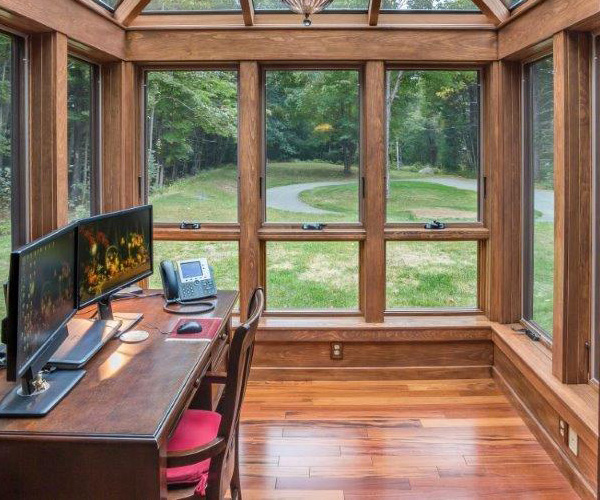 An interior view of a glass conservatory office space with composite flooring in North Hampton, New Hampshire