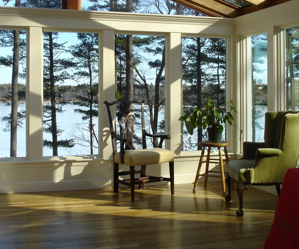 The seating area of a gable-style sunroom featuring oak hardwood flooring and a beautiful lakeside view in Stoneham, Massachusetts
